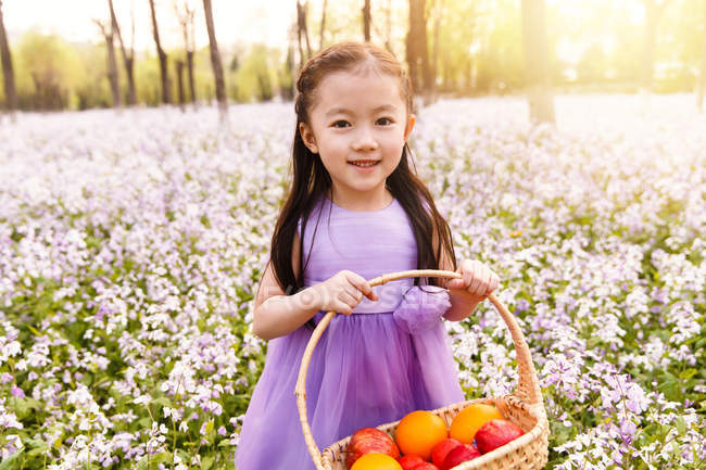 Adorable asian kid in dress holding basket with easter eggs at flower field — Stock Photo