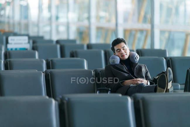 Jeune homme d'affaires asiatique dormir à l'aéroport — Photo de stock