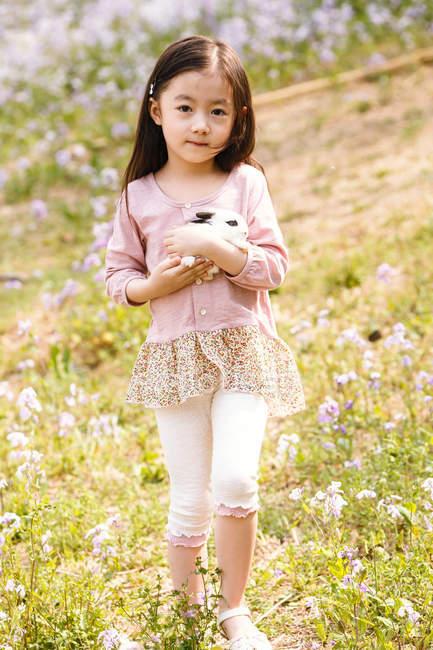 Adorável asiático criança segurando bonito coelho ao ar livre — Fotografia de Stock