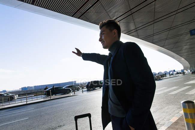 Jungunternehmer erwischt Taxi am Flughafen, Tieffliegerblick — Stockfoto