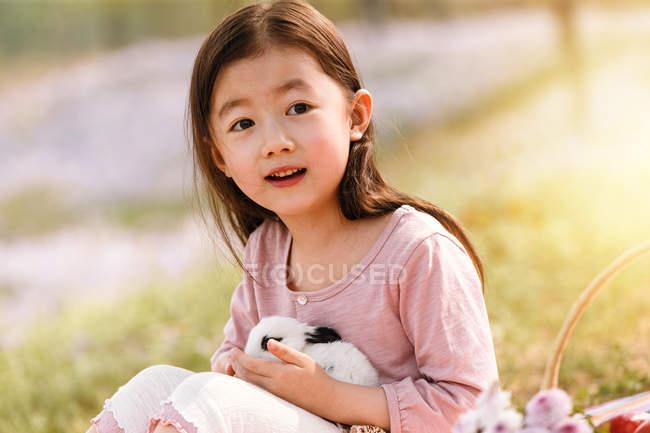 Entzückende asiatische Kind hält niedliche Kaninchen im Freien — Stockfoto