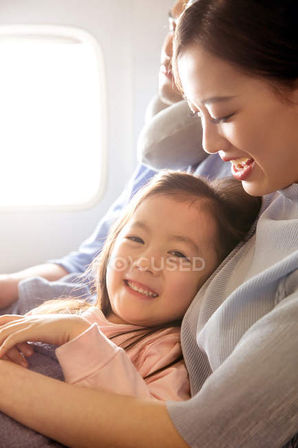 Happy family with one child traveling by plane, girl smiling at camera — Stock Photo