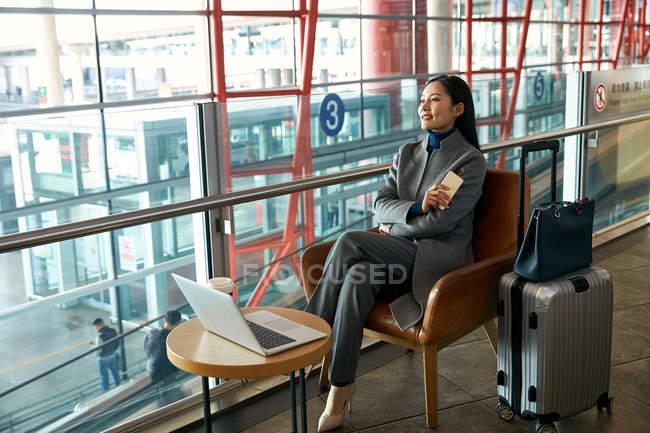 Красивая молодая деловая женщина с ноутбуком и смартфоном в зале ожидания аэропорта — стоковое фото