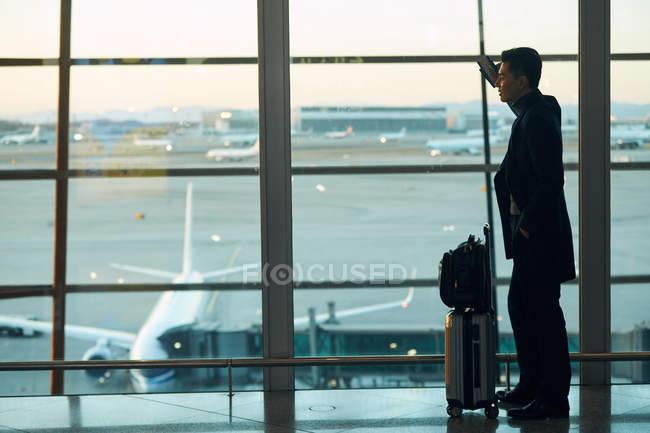 Vue latérale du jeune homme d'affaires avec bagages à l'aéroport — Photo de stock