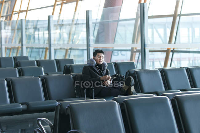Young asian businessman sleeping at the airport — Stock Photo