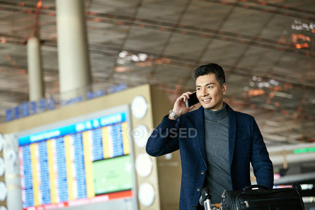 Young businessman talking by smartphone at the airport — Stock Photo