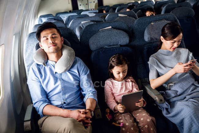Happy family with one child traveling by plane, high angle view — Stock Photo