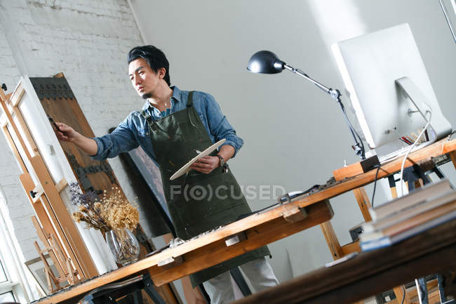 Focused male artist in apron holding palette and painting picture in studio, low angle view — Stock Photo