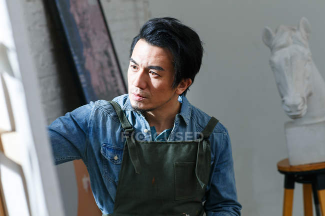 Concentrated male artist painting picture in studio — Stock Photo