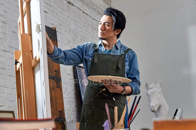 Focused male artist holding palette and painting picture in studio — Stock Photo