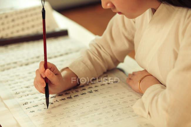 Tiro cortado de mulher escrevendo caracteres chineses com escova de caligrafia — Fotografia de Stock