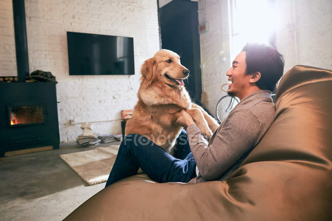 Side view of happy asian man sitting on bean bag chair and playing with dog at home — Stock Photo