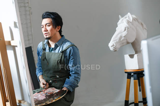 Asian male artist in apron holding palette and painting picture in studio — Stock Photo