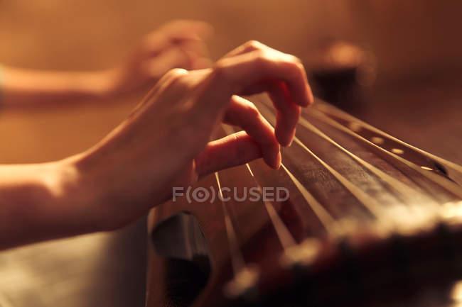 Schnappschuss einer Frau, die ein traditionelles altes chinesisches Saiteninstrument spielt — Stockfoto