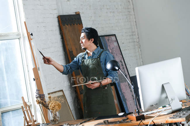 Concentrated asian artist holding palette and painting picture in studio — Stock Photo
