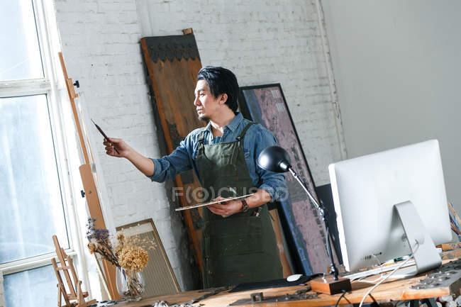Концентрований Азіатський виконавець тримає палітру та картини картину в студії — стокове фото