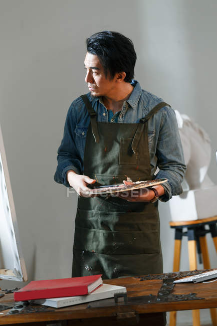 Serious asian artist in apron holding palette and looking at painting in studio — Stock Photo
