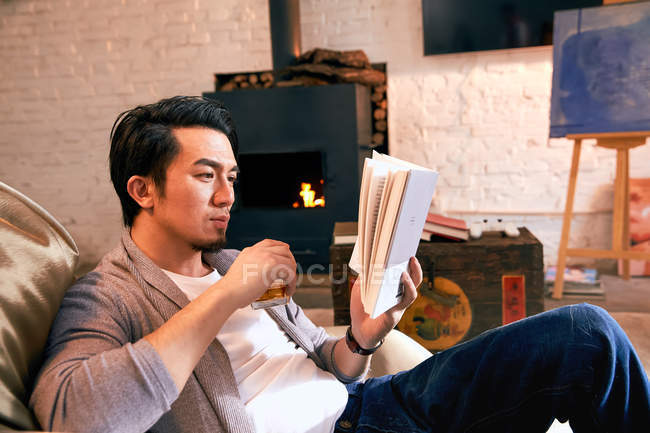 Focused asian man sitting on bean bag chair and reading book at home — Stock Photo