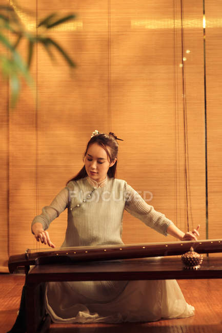 Focused young asian woman playing traditional chinese guzheng instrument — Stock Photo
