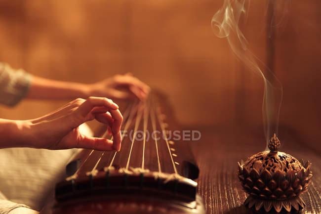 Schnappschuss einer Frau, die ein traditionelles chinesisches Guzheng-Instrument spielt — Stockfoto