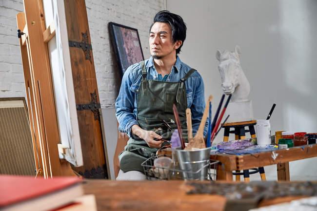 Nachdenklicher junger Maler betrachtet Bild im Atelier — Stockfoto
