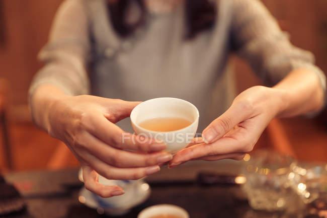Plan recadré de femme tenant une tasse blanche avec une tisane aromatique chaude — Photo de stock