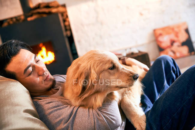 Schöner asiatischer Mann liegt auf Bohnensackstuhl und umarmt Hund zu Hause — Stockfoto