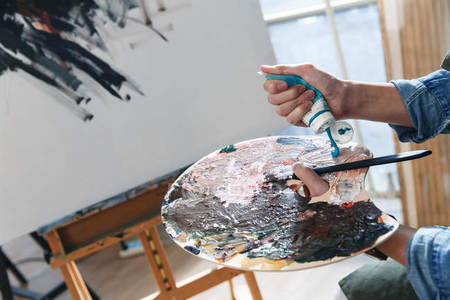 Cropped shot of male artist holding palette with paint tube in studio — Stock Photo