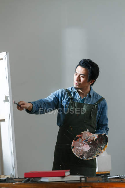 Handsome focused chinese artist in apron holding palette and painting picture in studio — Stock Photo