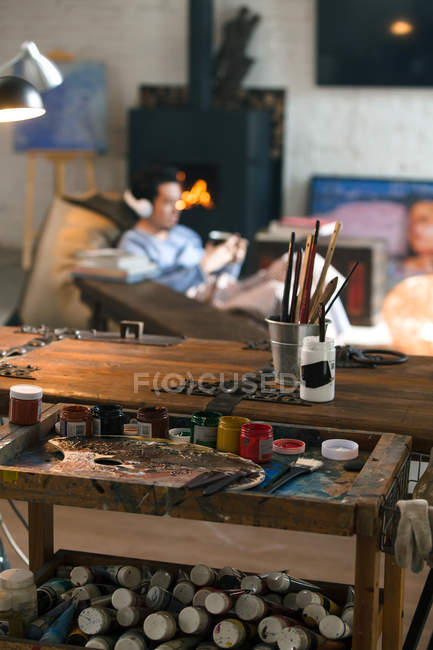 Close-up view of art tools and young man in headphones sitting near fireplace — Stock Photo