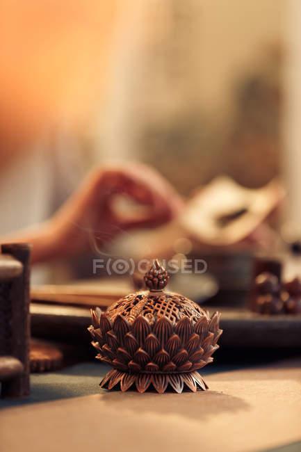 Vue rapprochée de la décoration asiatique traditionnelle parfumée et femme tenant du thé séché derrière, mise au point sélective — Photo de stock