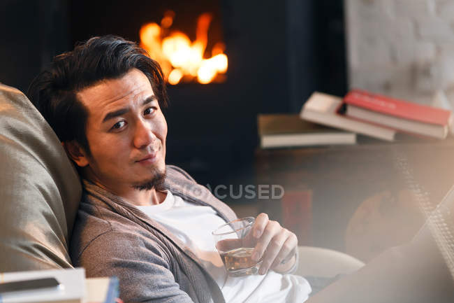 Selective focus of handsome asian man holding glass of whiskey and smiling at camera at home — Stock Photo
