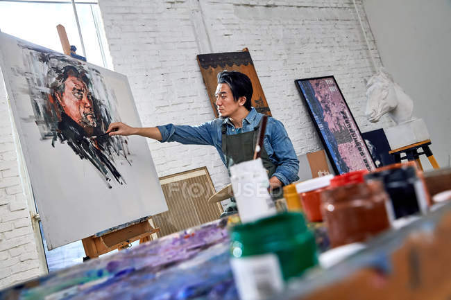 Focused young male artist painting picture in art studio — Stock Photo