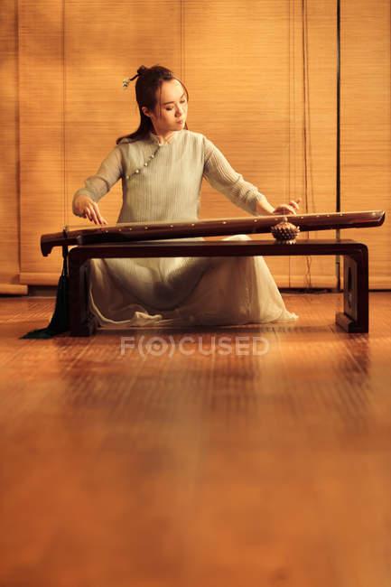 Fokussierte junge Asiatin spielt traditionelles chinesisches Guzheng-Instrument — Stockfoto
