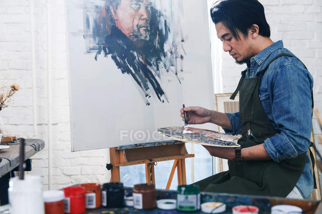 Handsome asian male artist in apron holding palette and painting portrait in studio — Stock Photo