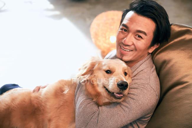 Aus der Vogelperspektive: fröhlicher asiatischer Mann umarmt Hund und lächelt zu Hause in die Kamera — Stockfoto