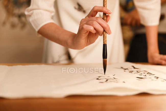 Close-up visão parcial da mulher com escova de caligrafia e escrita de caracteres chineses — Fotografia de Stock