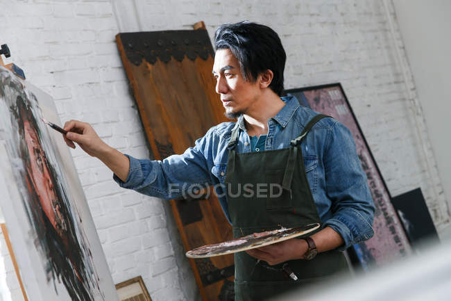 Side view of concentrated male artist painting portrait in studio — Stock Photo