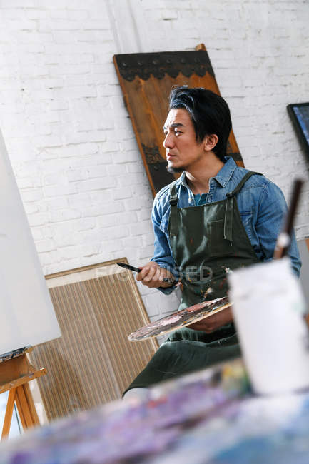Thoughtful male painter in apron holding palette and looking at easel in studio — Stock Photo