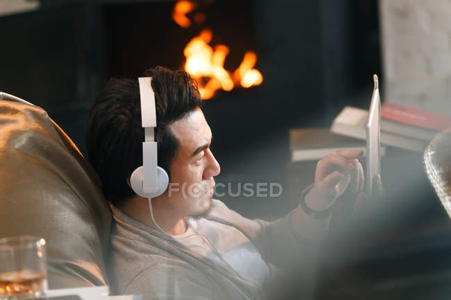 Selective focus of young asian man in headphones using digital tablet at home — Stock Photo