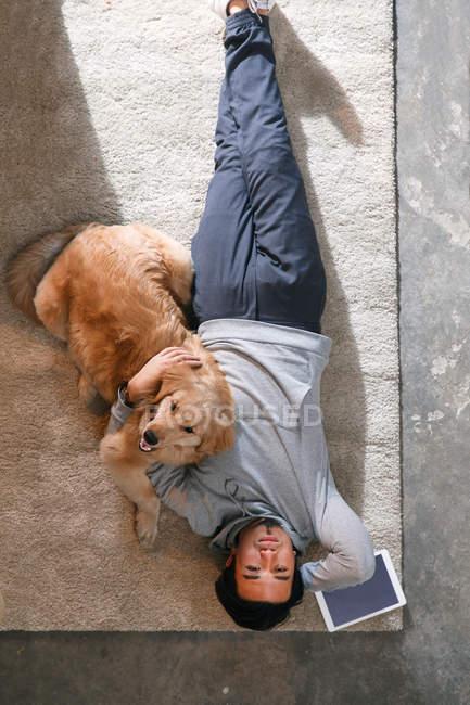Вид зверху людини, лежачи з собакою на килимовій доріжці і дивлячись на камеру — стокове фото