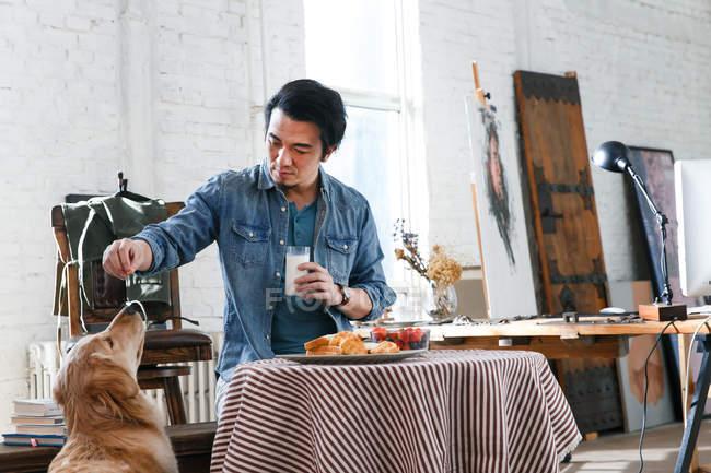 Beau chien asiatique d'alimentation d'homme pendant le petit déjeuner dans l'atelier d'art — Photo de stock