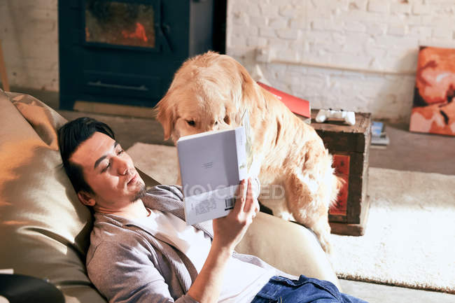 High angle view of young asian man reading book and playing with dog at home — Stock Photo