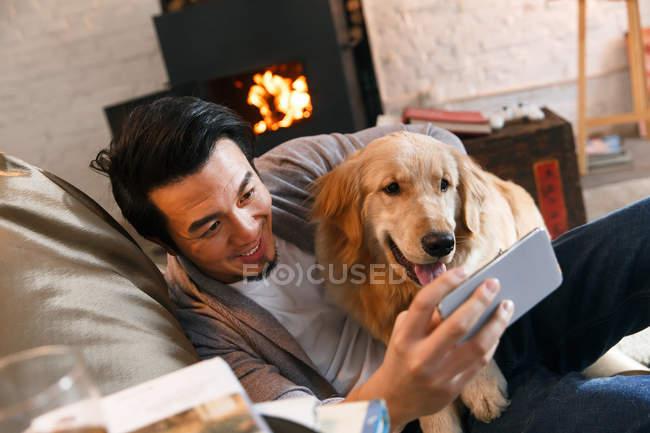 Felice uomo asiatico abbracciare cane e utilizzando smartphone a casa — Foto stock