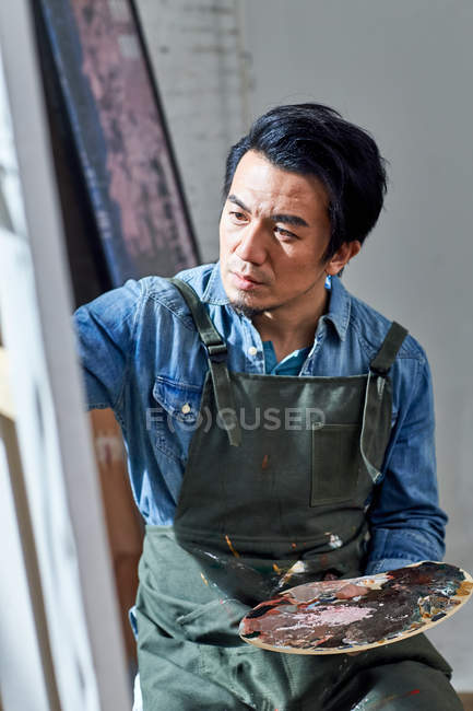Concentrated male artist in apron holding palette and painting picture in studio — Stock Photo