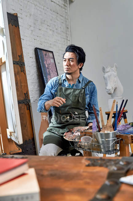 Serious male artist in apron holding palette and painting picture in studio — Stock Photo