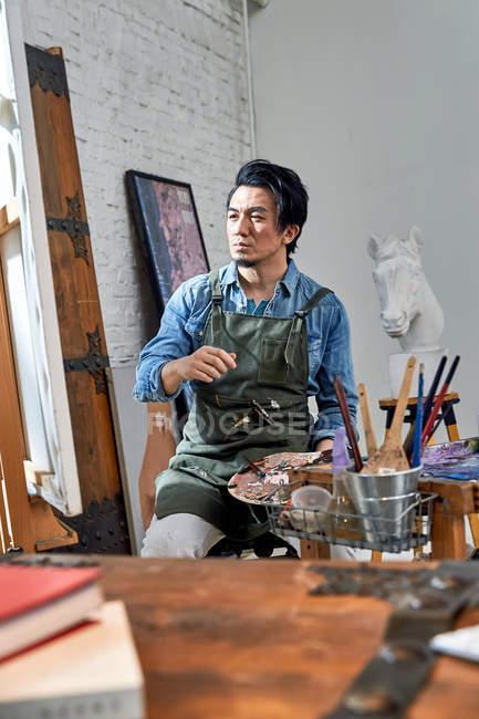 Ernsthafter männlicher Künstler in Schürze mit Palette und Malerei im Atelier — Stockfoto