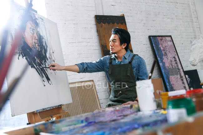 Focused young male artist in apron painting portrait in studio — Stock Photo