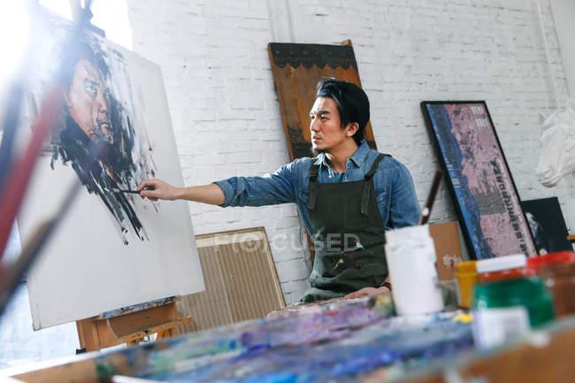 Fokussierte junge männliche Künstler in Schürze Malerei Porträt im Atelier — Stockfoto