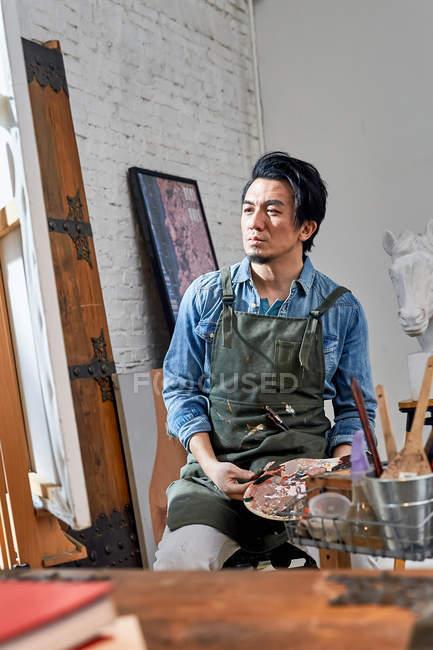 Ernsthafter asiatischer Künstler in Schürze mit Palette und Blick auf die Malerei im Atelier — Stockfoto